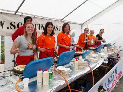 Een groep vrijwilligers die in de poffertjestent aan het bakken is.